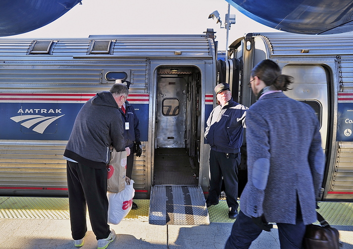 Conductors Brad Ritter, left, and Brian Labreck assist passengers as they board the Downeaster in Portland for a trip south to Boston.