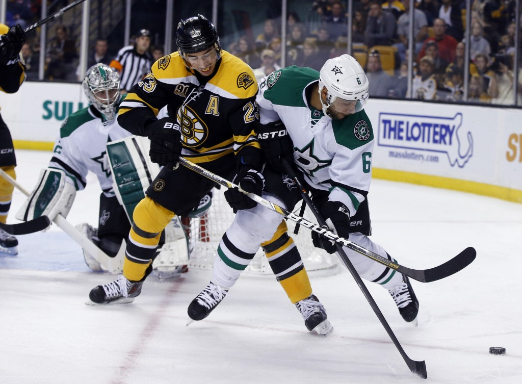 Boston Bruins center Chris Kelly tries to gain control of the puck as Dallas Stars defenseman Trevor Daley defends while Stars goalie Kari Lehtonen watches at left during the second period Tuesday night in Boston.
