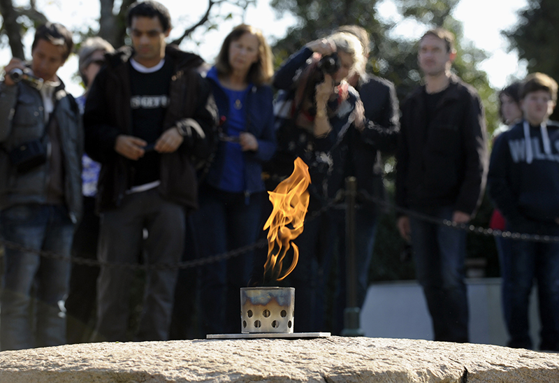 In this Tuesday, Oct. 29, 2013 file photo, visitors stand near the eternal flame at the grave site of U.S. President John F. Kennedy at the Arlington National Cemetery in Arlington, Va. The cemetery transferred the flame from a temporary burner to the restored permanent eternal flame that is part of a memorial to the 35th president. Repairs began in April 2013 to replace components of the eternal flame's burner.