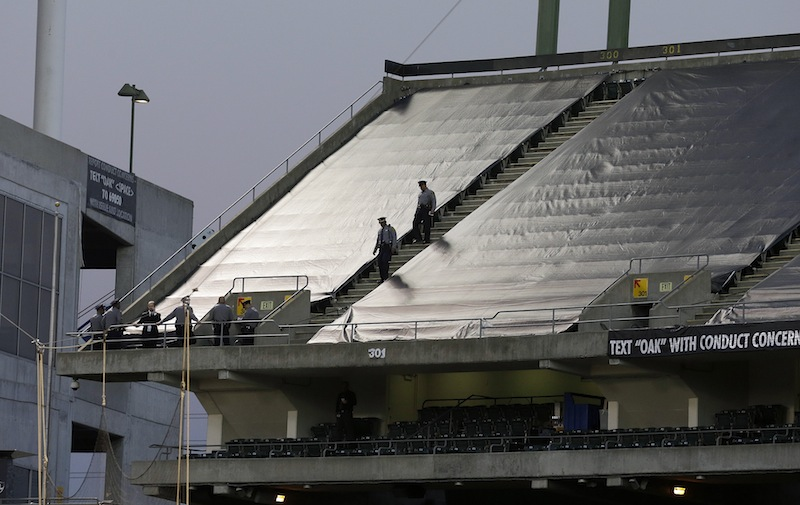Law enforcement officials walk in the upper deck of O.co Coliseum after an NFL football game between the Oakland Raiders and the Tennessee Titans in Oakland, Calif., Sunday, Nov. 24, 2013. A woman who jumped from the third level of the Oakland Raiders' stadium survived after a man tried to catch her and broke her fall, authorities said. NFLACTION13;