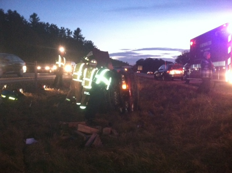 Maine State Troopers attend to an overturned car Wednesday night after an alleged hit-and-run crash on southbound I-295 in Cumberland.