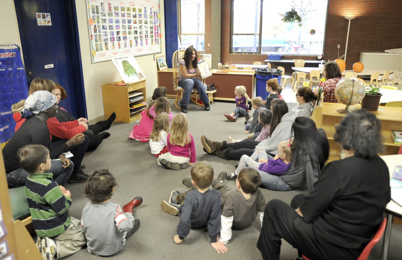 Preschoolers listen to their teacher read a story. Children who start learning earlier do better in school and in life.