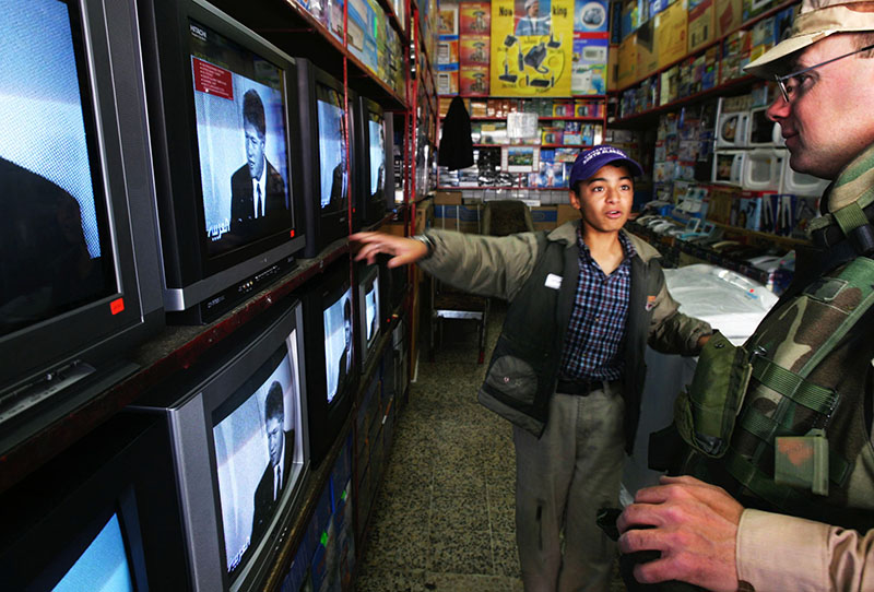 Staff photo by Gregory Rec -- Sunday, April 25, 2004 -- Hakem Omar, a 13-year-old Kurdish boy who speaks English well, tells Sgt. John Keene of Danville Junction the price for a television set in a store in Dohuk on Sunday. Because of his English skills, the teen helps soldiers shop and bargain for lower prices. And yes, that's Bill Clinton on the television sets. Inside Iraq