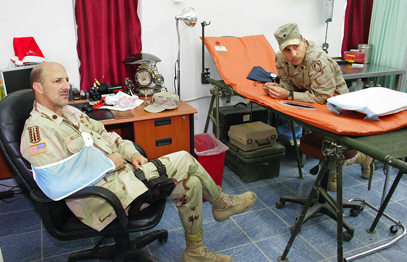 "Staff photo by Gregory Rec -- Wednesday, December 22, 2004 -- Maj. John ""Doc"" Nelson, left, talks with medics Wednesday in the treatment room at the 133rd Engineer Battalion's aid station on FOB Marez. At right is Spc. Ronald Cyr of Lewiston. Maine soldiers injured in Iraq Maine soldiers killed in Iraq"