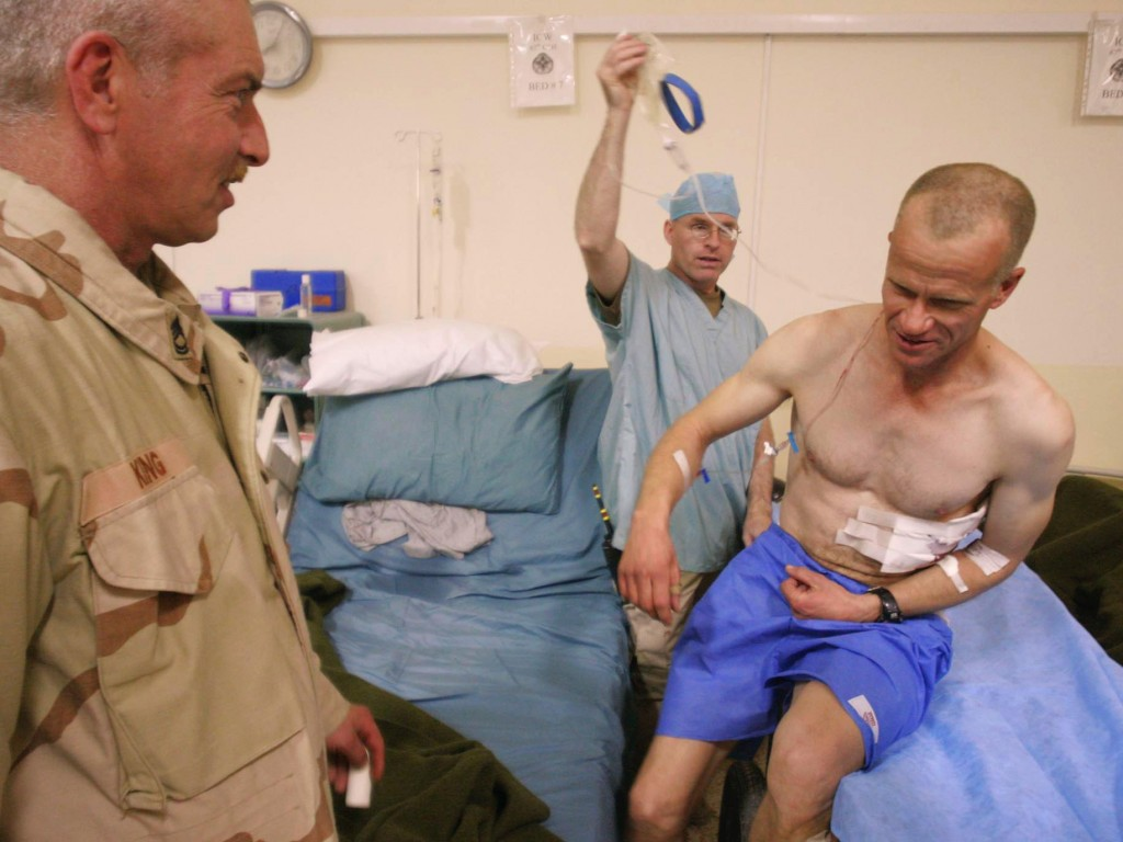 Staff photo by Gregory Rec -- Tuesday, December 21, 2004 -- On his way to surgery, Sgt. Christopher Rushlau moves onto a guerney under his own power at the 67th Combat Support Hospital in Mosul, Iraq on Tuesday night. Rushlau, a soldier with the 133rd Engineer Battalion, suffered shrapnel wounds in the attack at the dining facility at FOB Marez on Tuesday. At left is Sgt. 1st class Wayne King. Maine soldiers injured in Iraq