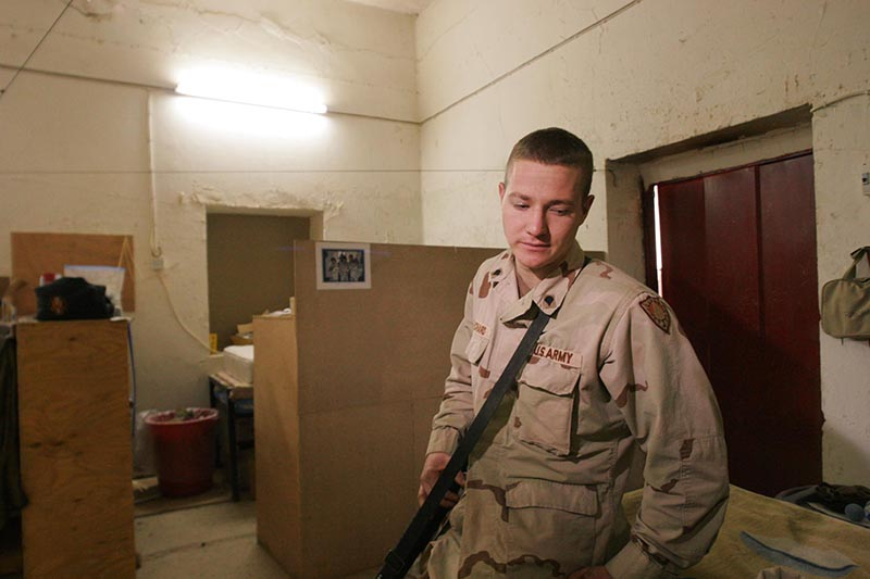 Staff photo by Gregory Rec -- Thursday, December 23, 2004 -- Greg Raychard of Buxton pauses while talking about his friend and roommate Thomas Dostie, whose cubicle is in the background. Raychard and Dostie shared this room at FOB Marez with two other soldiers.