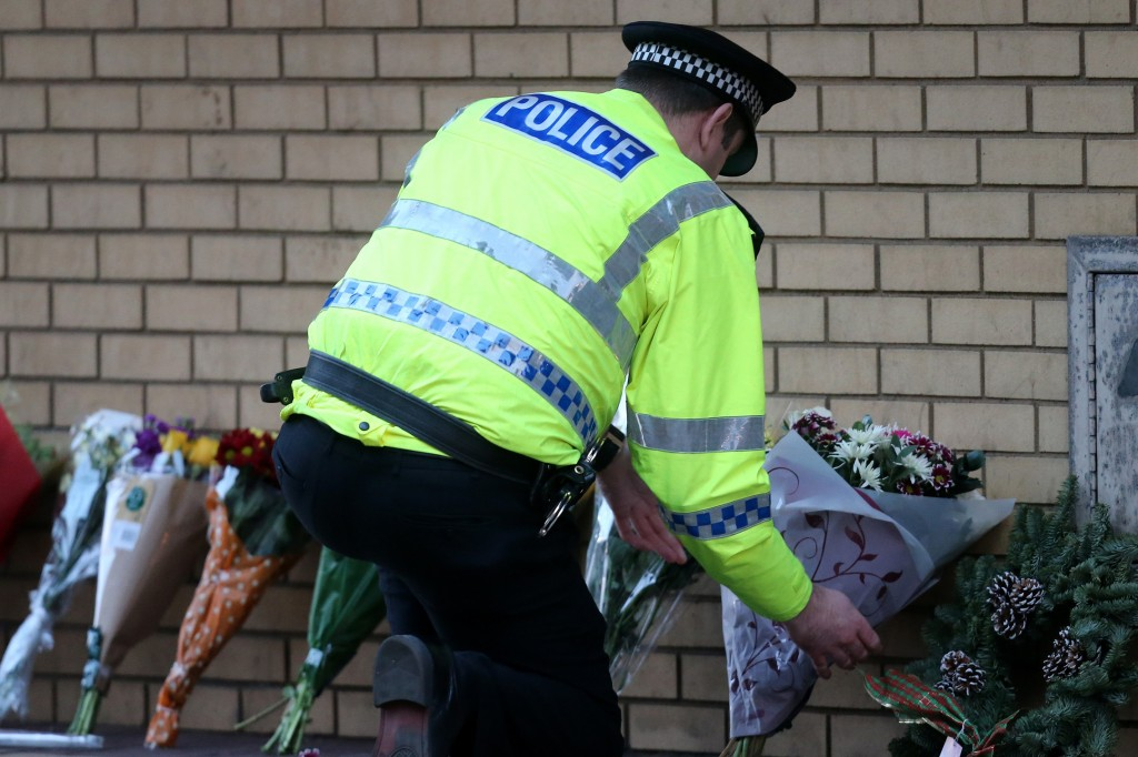 An officer arranges flowers Saturday after a helicopter crash at The Clutha pub in Glasgow, Scotland. A rescue and recovery operation is ongoing and could bring more bad news.