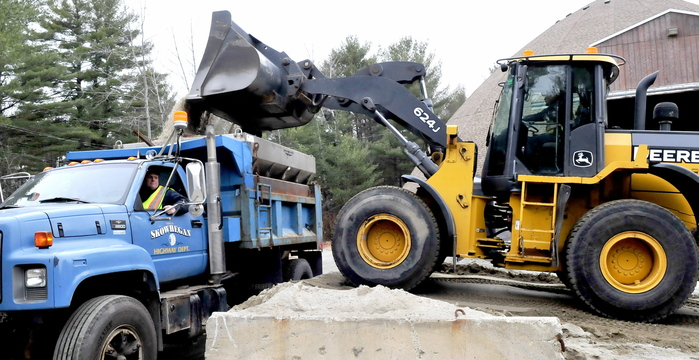 Skowhegan Highway Department employees Jason Kirk, in truck, and Duane Whittemore team up Tuesday at the town's sand shed to get a mixture of sand and salt loaded for treating roads in anticipation of Wednesday's storm.