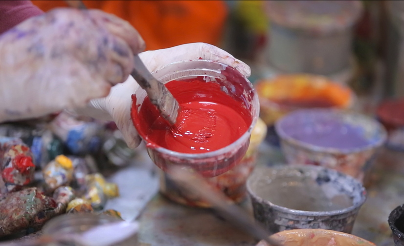 Holley Mead, a studio assistant to Jon Imber, mixes a shade of red before the artist begins a portrait in his Stonington studio last month. After being diagnosed with ALS last year, Imber has relied on Mead and others in his creative process.