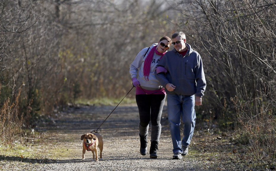 Meghan O'Brien, 31, left, takes a walk in the woods with her dad, Ken O'Brien, and their dog, Max, at Raceway Woods Forest Preserve in Carpentersville, Ill., Nov. 19. She is fighting both lung cancer and the condemnation that often comes with it.