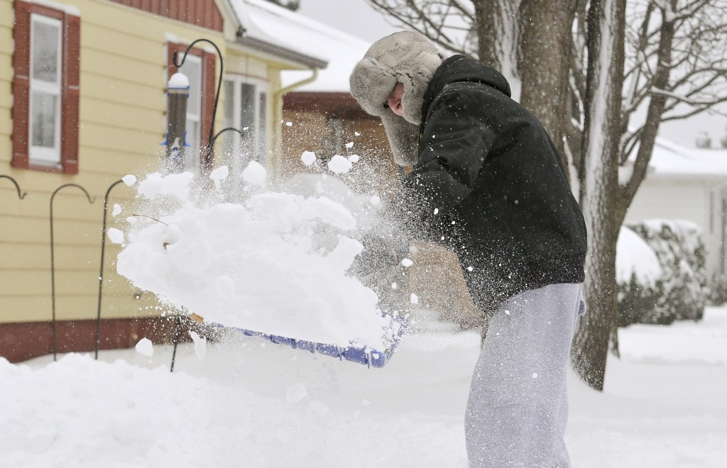 Andrew Wooster clears off his driveway in Virginia, Minn. Tuesday. The storm is due in part to the jet stream dipping south, allowing frigid arctic air to rush in.