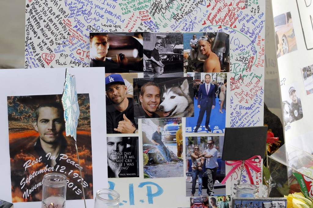Photos and messages are seen at a roadside memorial at the site of the auto crash that took the life of actor Paul Walker and friend Roger Rodas, in Valencia, Calif.