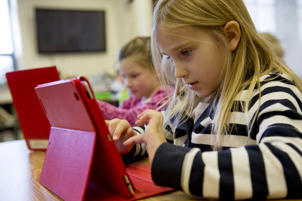 Ella Russell, 7, works on an iPad in her second-grade class at Jamestown Elementary School in Arlington, Va. Many schools need faster and more reliable Internet access.