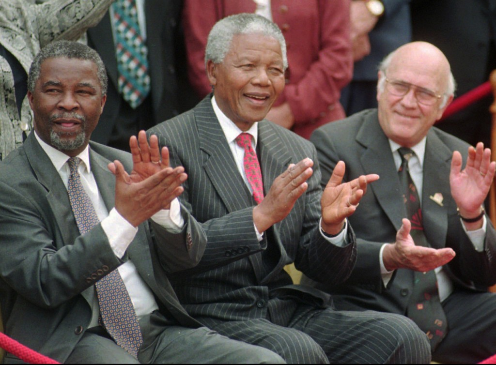 FILE - In this May 8, 1996 file photo, South African President Nelson Mandela, center, applauds along with his two deputy presidents, Thabo Mbeki, left, and F.W. de Klerk, after a new constitution was approved by the Constitutional Assembly in Cape Town, South Africa. South Africa's president Jacob Zuma says, Thursday, Dec. 5, 2013, that Mandela has died. He was 95. (AP Photo/Argus, Leon Muller, File)