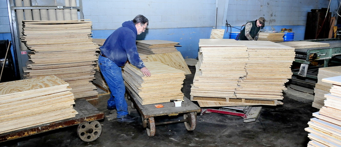 Cousineau Wood Products employees Darrell Clark, left, and Jerry Chestnut work on flooring stock at the North Anson company on Thursday.
