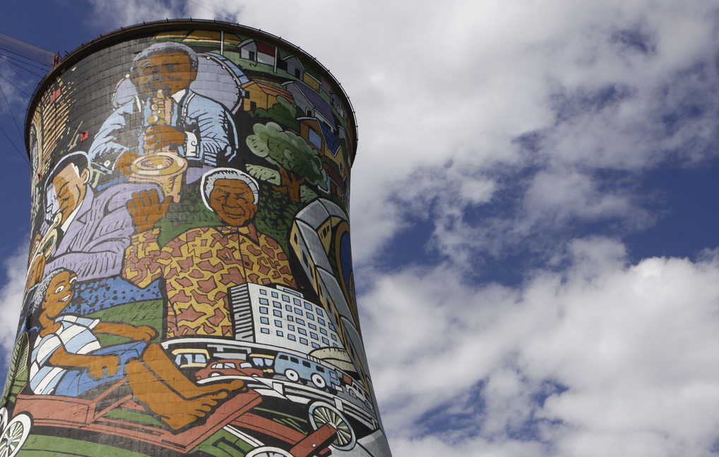 A portrait of former President Nelson Mandela adorns the center of a mural on a cooling tower of a defunct power station in Soweto, South Africa, in this Dec. 10, 2012 file photo. On Thursday, Dec. 5, 2013, Mandela died at the age of 95.