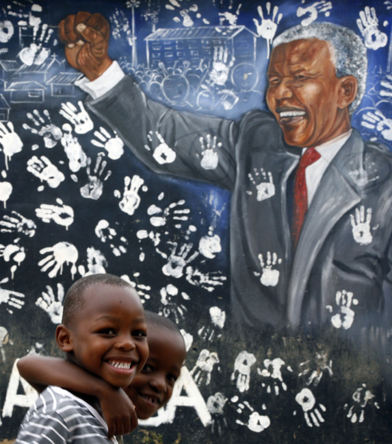 Two boys walk past a mural depicting former South African President Nelson Mandela at the Alexandra township in Johannesburg, South Africa, in this Dec. 11, 2012 file photo. On Thursday, Dec. 5, 2013, Mandela died at the age of 95.