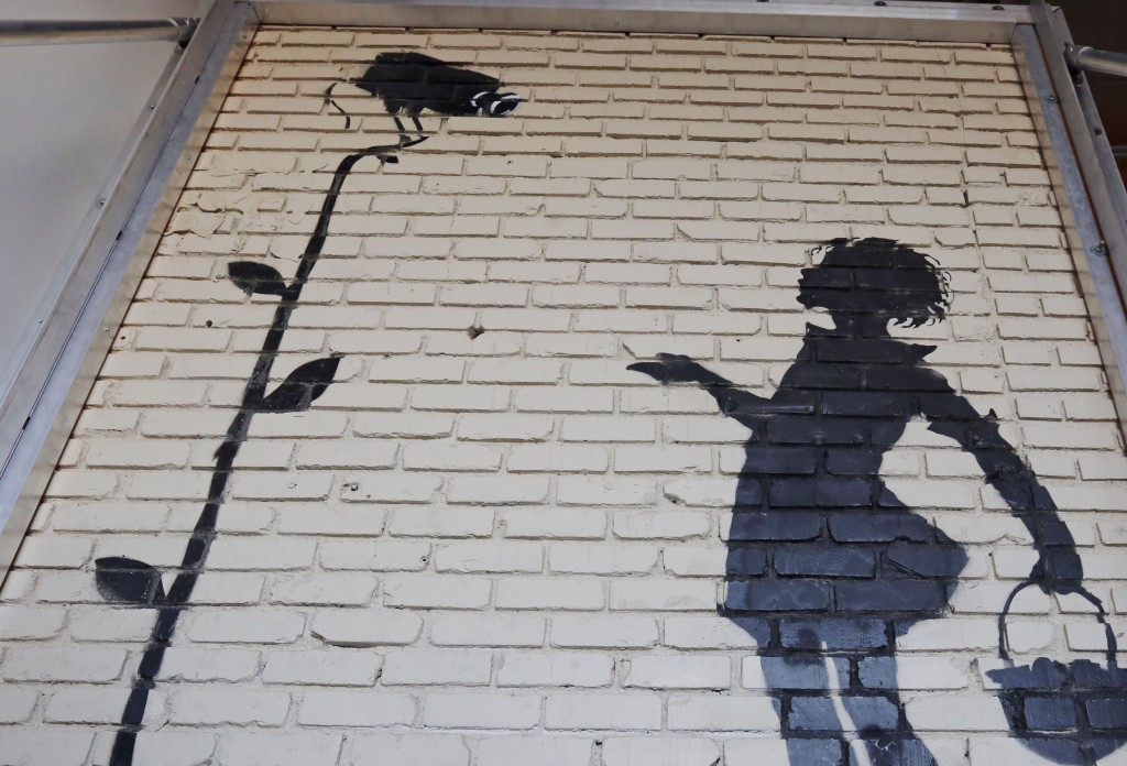 """""""Flower Girl,"""" a delicate stencil on a massive brick wall by popular street artist Banksy, is shown on display."""