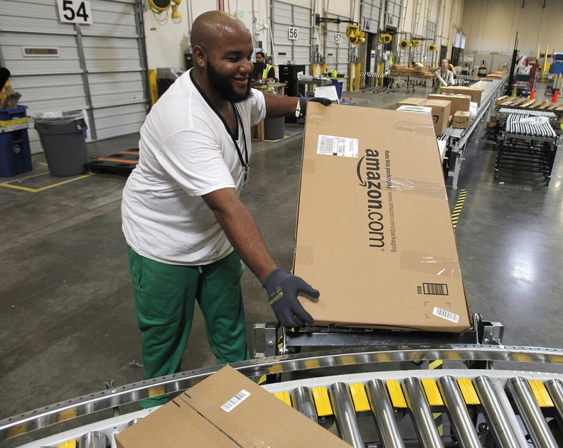 An employee places a package on the belt at an Amazon.com fulfillment center in Goodyear, Ariz., in 2010. A reader says taxes on online sales would not be new since there is already a use tax.