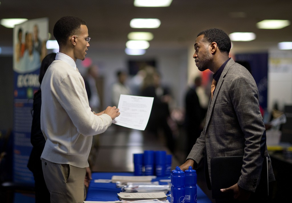 Retired Air Force Master Sgt. Thomas Gipson, right, of Atlanta talks about his resume last month with Ralph Brown, an analyst with the Centers for Disease Control and Prevention, during a job fair for veterans in Marietta, Ga. The U.S. job market is finally showing signs of consistent gains.