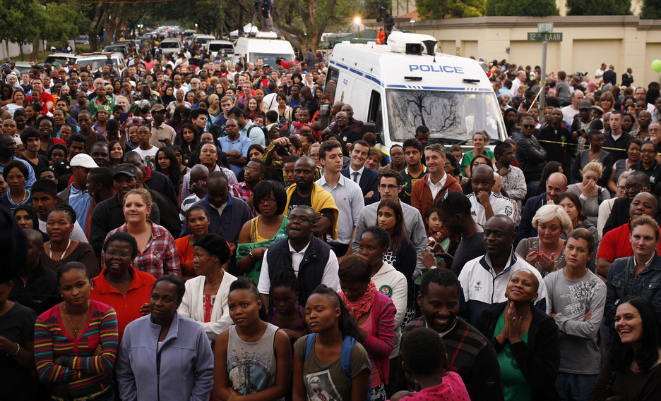People gather for a prayer service outside the home of former president Nelson Mandela in Johannesburg, South Africa, on Friday. Mandela passed away Thursday night after a long illness. He was 95.