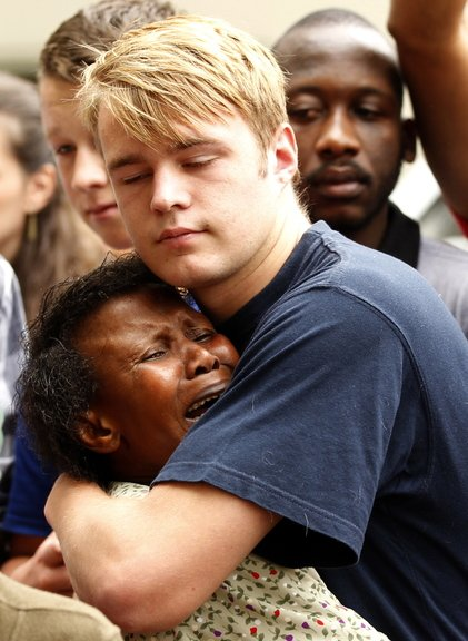 People comfort each other outside the residence of former South African President Nelson Mandela in Johannesburg on Friday.