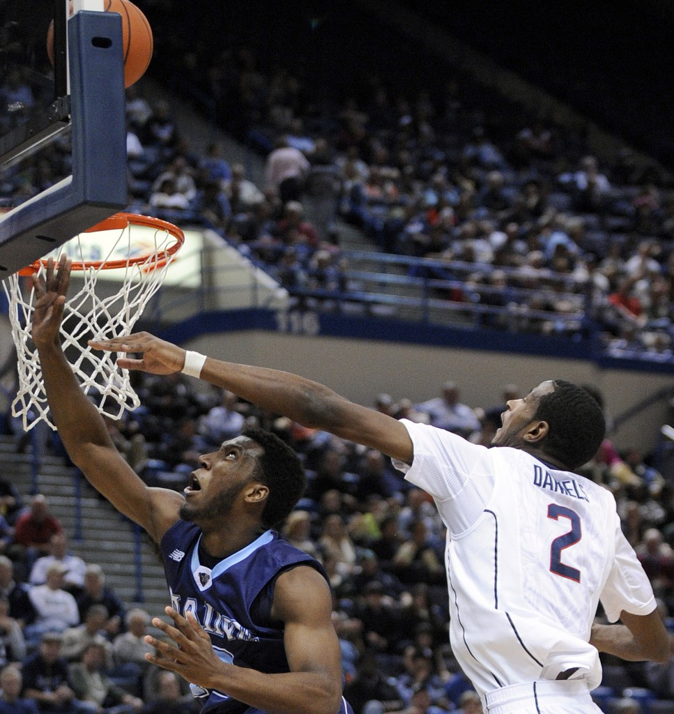Maine's Xavier Pollard, left, is fouled by Connecticut's DeAndre Daniels as he goes to the basket during the first half of Connecticut's 95-68 win at Hartford, Conn., on Friday.