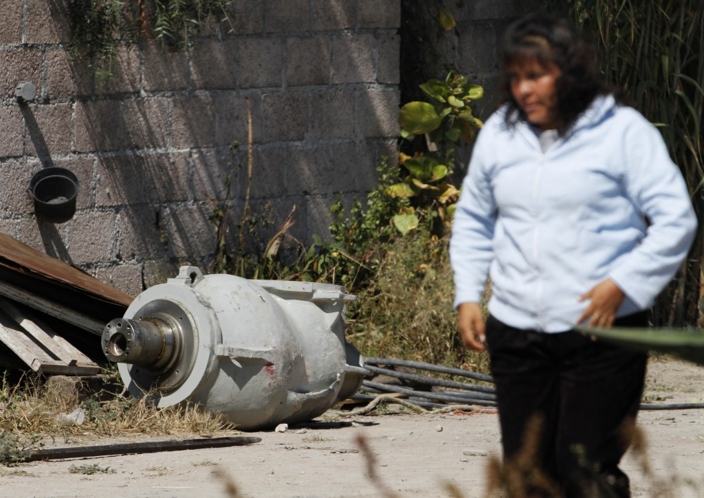 A woman walks near part of a radiation therapy machine in the patio of the family that found the abandoned equipment in a nearby field in the village of Hueypoxtla, Mexico, on Thursday. Officials were engaged in the delicate task of recovering the stolen shipment of highly radioactive cobalt-60 abandoned in a rural field in central Mexico state.