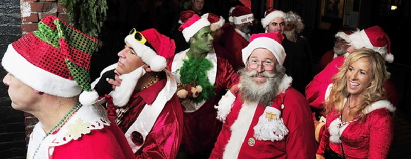 Santas and elves wait in line at Oasis on Wharf Street in Portland's Old Port as part of the Santacon pub crawl and fundraiser Saturday.