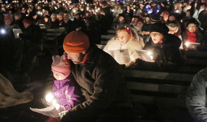 Jeff LaCouse of Boothbay Harbor and his daughter Alana, 4, sing carols at the Franciscan monastery in Kennebunk on Saturday. More than 1,000 people took part.