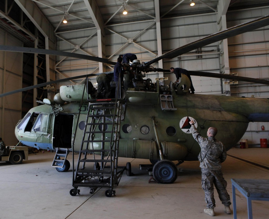 Sgt. Troy Bencke, right, points toward Afghan air force engineers as they work on an Mi-17 helicopter inside a hangar in Kabul, Afghanistan, in this April 6, 2010, file photo.