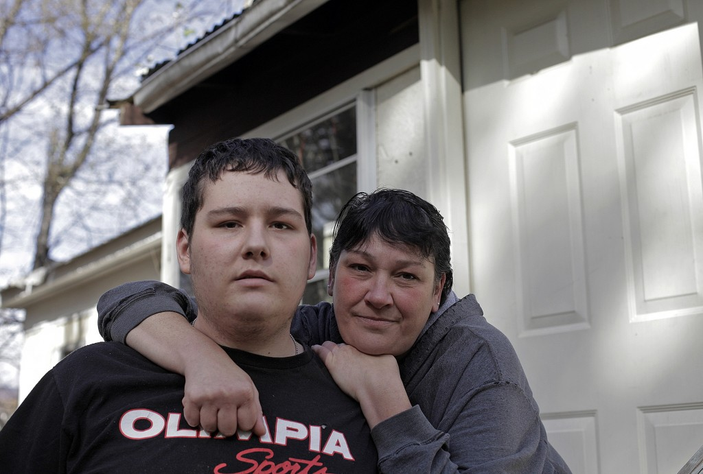 "Eighteen-year-old James Reynolds and his mother, Julie, pose at their West Paris home in mid-October, four months after he was shot three times in a confrontation with Maine State Trooper Jason Wing. Julie says she relives the shooting every day, trying to understand what happened. ""James has had a multitude of people who let him down, including me,"" Julie said. ""We didn't recognize (the mental illness) until it was too late."""