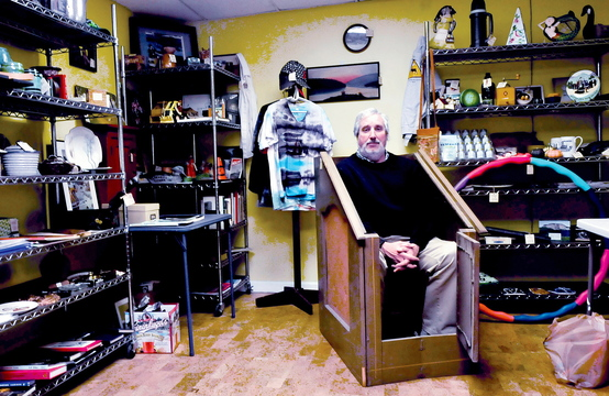 Iver Lofving sits inside an anidrosis box at his pop-up store in the Somerset Grist Mill in Skowhegan, where for two weeks he plans to sell a variety of unusual and locally themed items. The box was used in the 19th century to induce patient to perspire and induce healing.