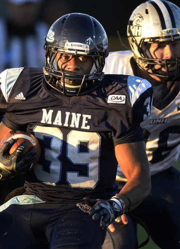 Rickey Stevens of Maine strides down the field in the fading afternoon light, away from Hayden Knudson of New Hampshire.