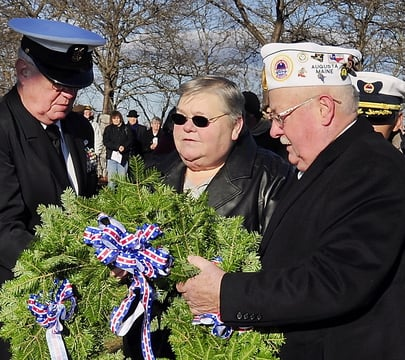 Navy veteran Gene Foster, left, and James E. Laflin, Maine AMVETS commander, help Jo Davis, widow of Pearl Harbor veteran Bert Davis, place a wreath honoring veterans during the Pearl Harbor Day Remembrance Service at Loring memorial park on the Eastern Promenade in Portland on Saturday.