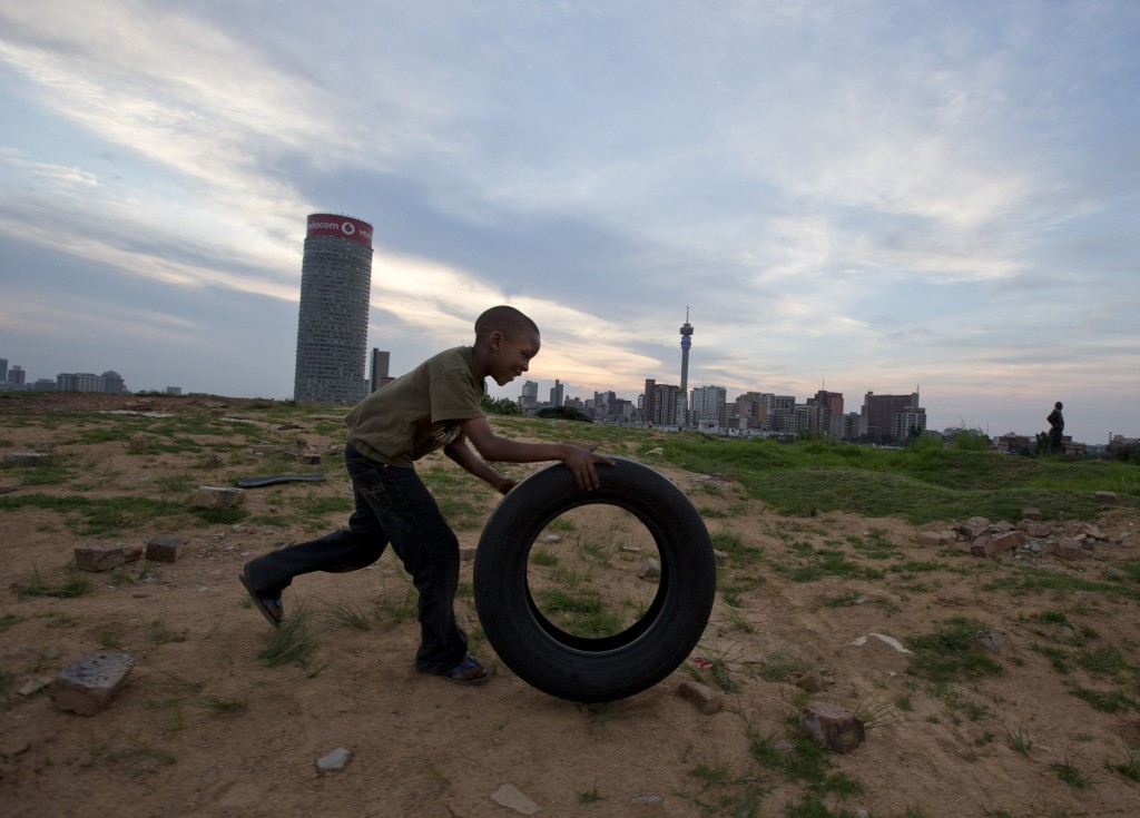 A boy plays with a rubber tire on a hill overlooking Johannesburg on Saturday. South Africa is no blissful paradise as it struggles with a staggering rate of violent crime. It has the world's highest incidence of HIV infection. And it harbors a wide income inequality.