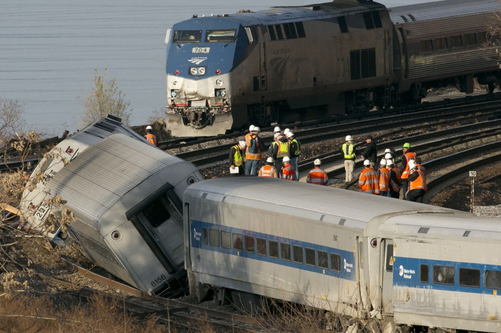 An Amtrak train, top, traveling on an unaffected track, passes a derailed Metro-North commuter train in the Bronx borough of New York on Dec. 1. Two federal lawmakers proposed Sunday that trains nationwide be outfitted with cameras pointed at engineers and at the tracks.