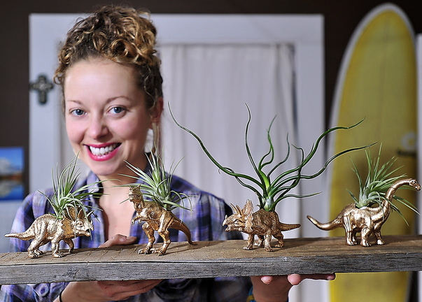 Brooke Hoerner with gold-painted dinosaur planters she creates in her Portland apartment. She's filled hundreds of orders for them since they were highlighted in Real Simple magazine.