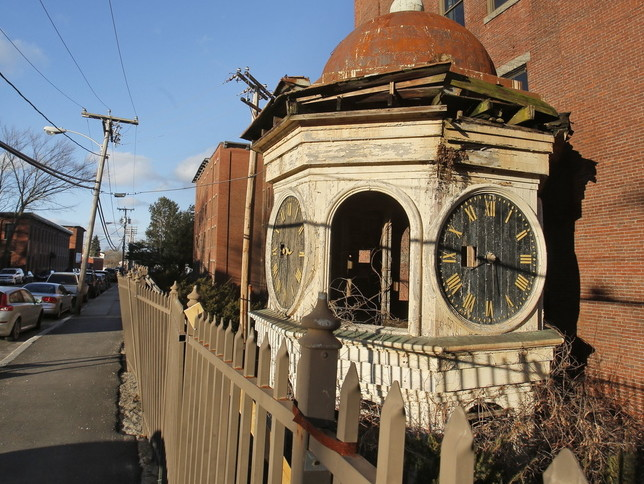 A historic clock tower rests on the ground next to the Lincoln Mill building in Biddeford, which it sat atop for 111 years before it was removed for safety reasons.