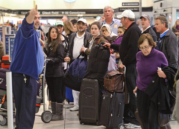 A US Airways agent directs travelers to another area to check on flight cancellations at Charlotte Douglas International Airport in Charlotte, N.C., on Sunday. Hundreds of passengers were delayed after numerous flights were canceled due to snowy and icy conditions around the country.