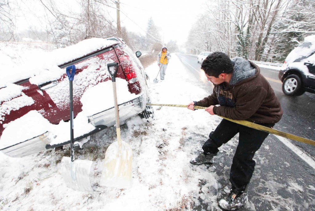 Juan Carlos tries to free his truck Sunday after it slid off Lancaster Pike in Wilmington, Del. The unexpectedly heavy snow led to a fatal crash in Pennsylvania involving 50 cars.