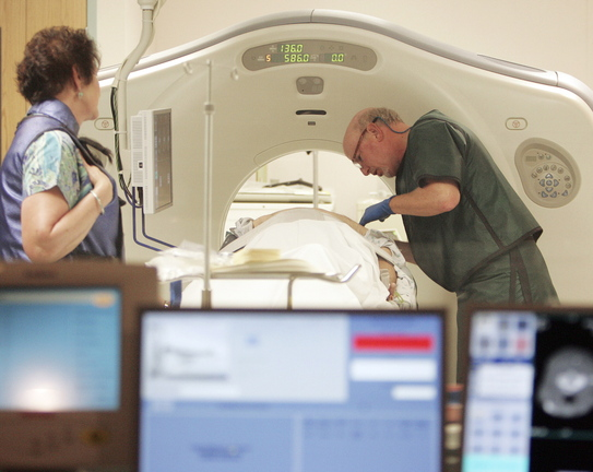In this June 3, 2010, file photo, Dr. Steven Birnbaum works with a patient in a CT scanner at Southern New Hampshire Medical Center in Nashua, N.H. A national study suggests the world's top cancer killer isn't always as deadly as doctors once thought, finding that more than 18 percent of lung cancers detected in screening scans are likely so slow growing that they'd never cause problems. But the provocative results are unlikely to change how doctors treat lung cancer.