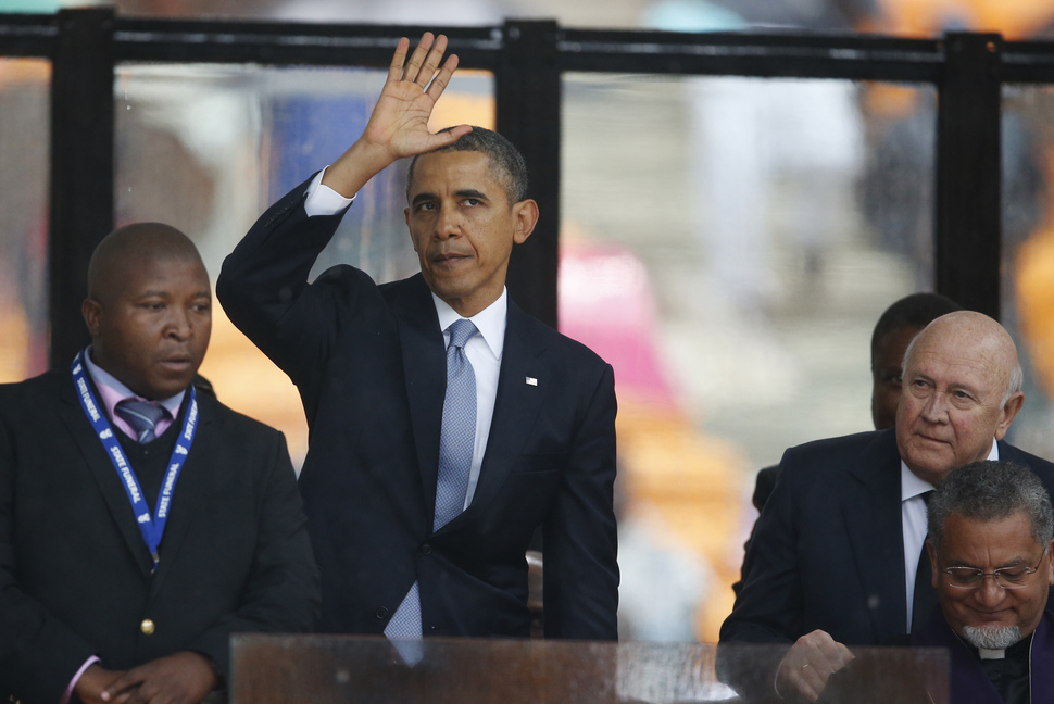 South Africa's last apartheid-era president, F.W. de Klerk, right, looks over as President Barrack Obama waves to mourners after speaking at the memorial service for former South African president Nelson Mandela at the FNB Stadium in Soweto near Johannesburg on Tuesday.
