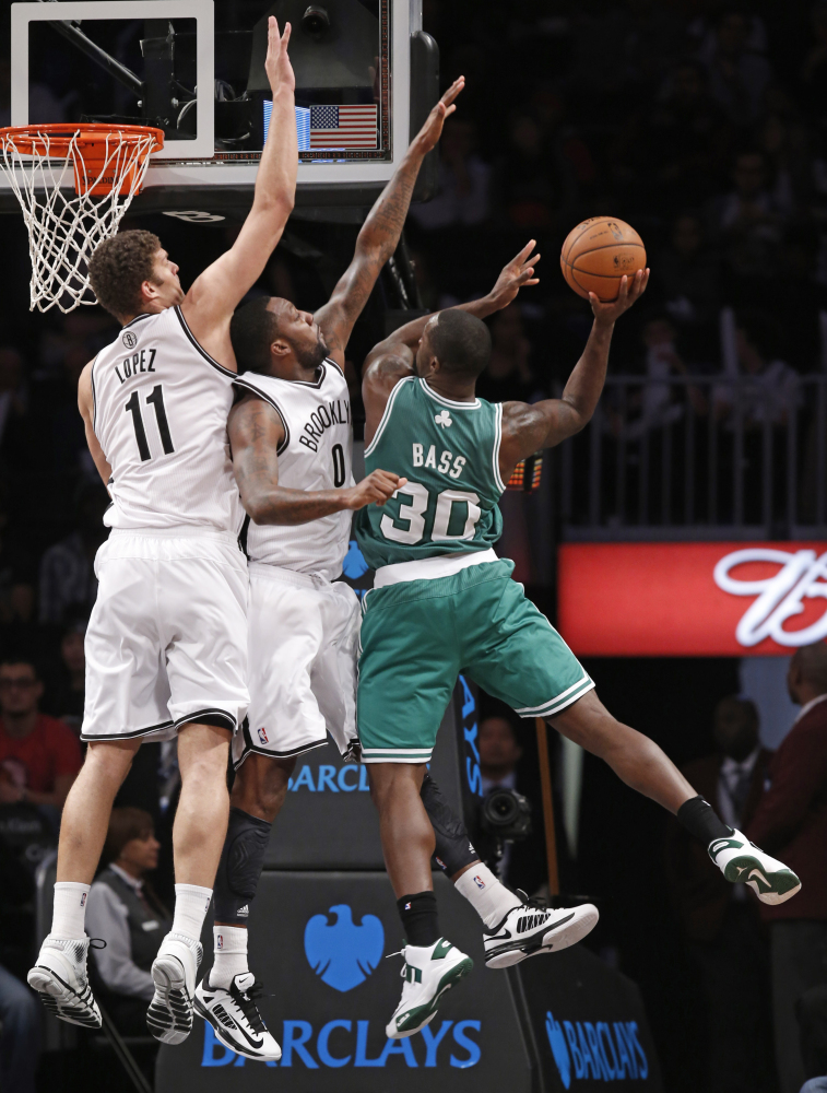 Brooklyn Nets Brook Lopez (11) and Brooklyn Nets Andray Blatche (0) defend Boston Celtics Brandon Bass (30) in the first half of their NBA basketball game, Tuesday, Dec. 10, 2013, in New York. (AP Photo/Kathy Willens)