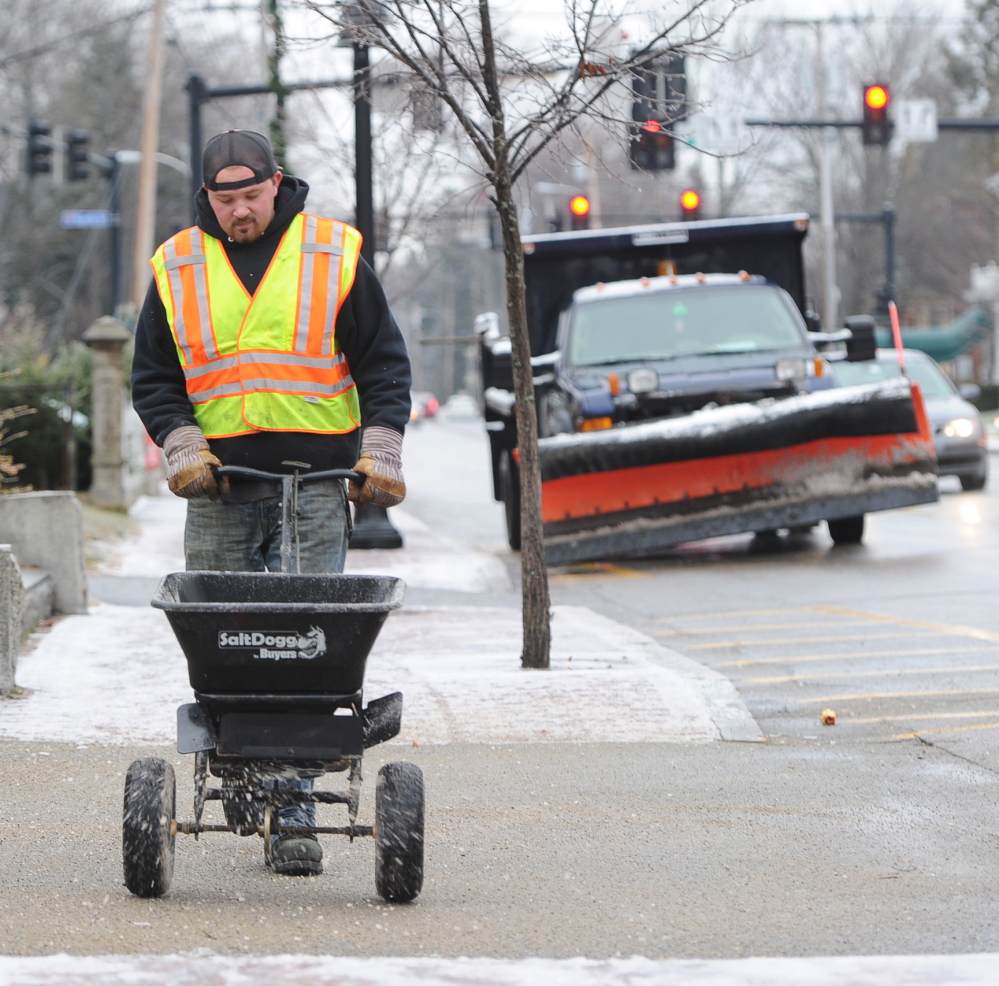 Saco Public Works employee Steve Aiken spreads salt on a Main Street sidewalk Tuesday after snow and sleet made for slick conditions throughout the region.