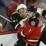 Boston Bruins' Jarome Iginla, left, tries to get past Calgary Flames' Kris Russell during the second period of an NHL hockey game in Calgary, Alberta on Tuesday.