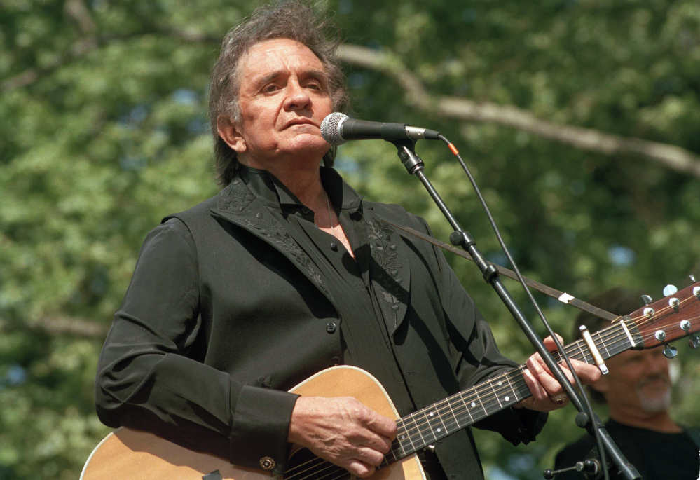 """File photo, Johnny Cash performs at a benefit concert in Central Park in New York. Cash's album, """"Out Among the Stars,"""" comprised of 12 studio recordings recently discovered, is releasing March 25, 2014."""