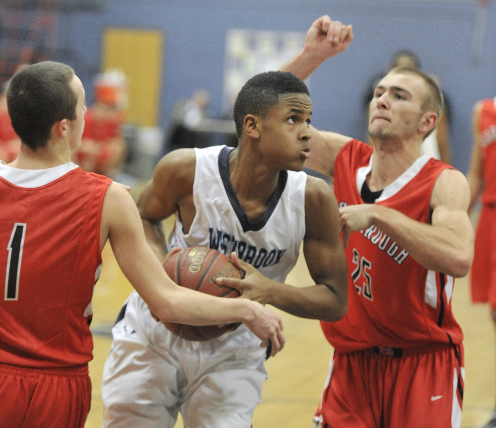 Westbrook's Demetrious Hoskins looks to drive between Scarborough defenders Sam Freeman (left) and Nate Wessel.