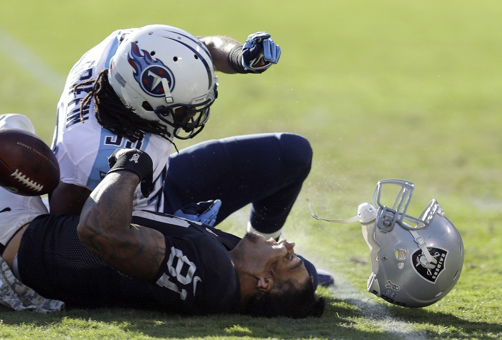 Oakland Raiders tight end Mychal Rivera loses his helmet after being hit by Tennessee Titans free safety Michael Griffin during a Nov. 14 game. Griffin was penalized on the play and served a one-game suspension for the hit.