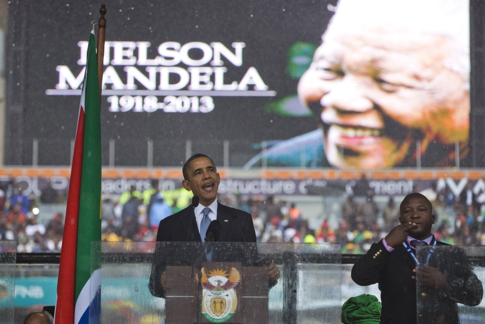 "President Barack Obama delivers his speech next to a sign language interpreter during a memorial service at FNB Stadium in honor of Nelson Mandela on Tuesday in Soweto. The national director of the Deaf Federation of South Africa says the interpreter was a ""fake."""
